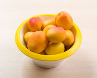 The simple food composition with apricot in the bowl on the unique backing closeup Stock Photos