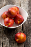 The simple food composition with nectarines on the unique backing closeup. Fresh summer fruits royalty free stock photo