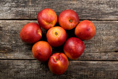The simple food composition with nectarines on the unique backing closeup. Fresh summer fruits stock images