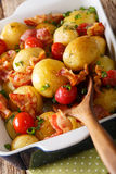 Simple food: new potatoes baked with bacon and tomatoes in bakin Royalty Free Stock Photos