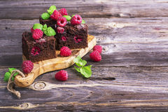 Simple fresh homemade brownies flavored with berries juicy  ripe raspberry on wooden background decorated  mint Royalty Free Stock Photo