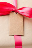 Simple gift. Close-up of a simple gift package with a red ribbon and small card Stock Image