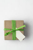 Simple Gift Box with Green Raffia Ribbon from Above. Overhead shot of a simple brown gift box, with green raffia ribbon and blank label on white background Royalty Free Stock Photography