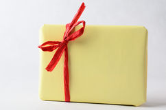 Simple Gift Package in Yellow with Red Raffia Ribbon. A gift package, very simply wrapped in plain yellow paper with red raffia ribbon tied to a bow.  No label Royalty Free Stock Photo