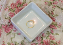 Simple gold solitaire engagement ring in white jewelry tray on v Stock Photography