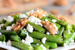 Simple green beans salad. Green beans warm salad with cottage cheese, crunchy walnuts, garlic and spices on a plate Royalty Free Stock Photography