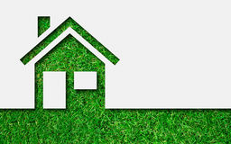Simple green eco house icon. On grass background Stock Photo