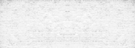 Simple grungy white brick wall with light gray shades pattern surface texture background in wide panorama banner format.  stock photo