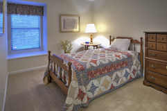 Simple guest bedroom. With twin bed and quilt Stock Photos