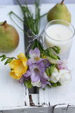 Simple hand tied posy of freesia. Simple hand tied posy of spring freesia flowers on a vintage wooden crate , with pears and a votive candle Stock Images