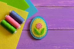 Small felt Easter egg decor with a pink flower, colored thread set, flat felt sheets on a purple wooden background. Simple handmade toy. How to hand sew a felt Royalty Free Stock Photo