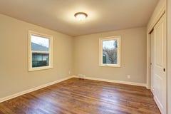 Simple hardwood floor bedroom with windows. Royalty Free Stock Image