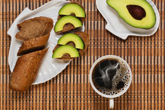 Simple healthy breakfast on the wooden mat. Simple original breakfast with brown baguette bread and sliced avocado and a mug of coffee on the wooden mat royalty free stock photos