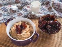 Simple healthy food. Oatmeal with dates and milk. Ramadan food Stock Photos