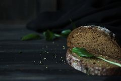 Simple and healthy food. Warm bread with a white dusting on a black wooden background Stock Photography