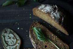 Simple and healthy food. Warm bread with a white dusting on a black wooden background Stock Photo