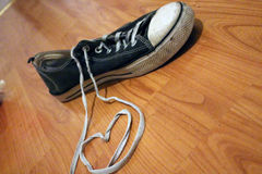 Simple heart and old blue sneaker. Sneaker shoe laces in the shape of a heart, on a wooden floor Stock Photo