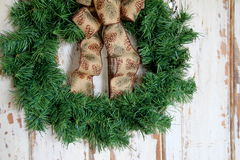 Simple holiday wreath with rustic ribbon on weathered door Stock Image