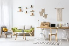 Simple home office with a desk. And living room interior decorated with macrame and plants stock photo