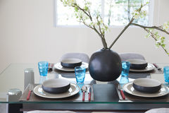 Simple home table setting. Glasses and cutlery and green plant Stock Photos