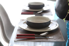 Simple home table setting. Glasses and cutlery and green plant Stock Image