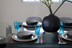Simple home table setting. Glasses and cutlery and green plant Royalty Free Stock Photography