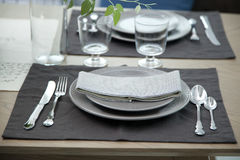 Simple home table setting. Glasses and cutlery and green plant Stock Photo