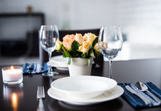 Simple home table setting. Glasses and cutlery, roses in a vase royalty free stock photo
