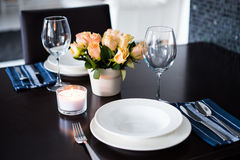 Simple home table setting. Glasses and cutlery, roses in a vase royalty free stock photography
