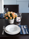 Simple home table setting. Glasses and cutlery, roses in a vase royalty free stock photos
