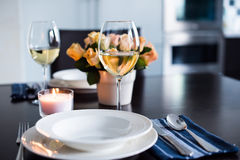 Simple home table setting. Glasses and cutlery, roses in a vase stock photos