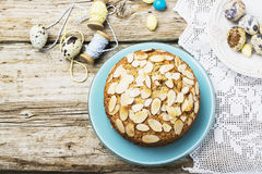 Simple homemade pecan pie decorated with petals of almond  a wooden background Serving Easter used blue and yellow. Simple homemade pecan pie decorated with Stock Images