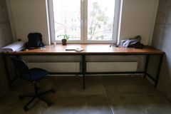 Well-equipped workplace with appliances in bright room with wind. Simple interior of working area. Simple and long table with brown wooden table-top and black Stock Photography
