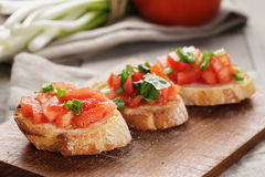 Simple italian appetizing bruschetta with tomato. On old table Royalty Free Stock Photography