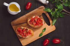 Simple italian appetizing bruschetta with tomato, on wooden tabl. E Royalty Free Stock Images