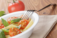 Simple italian pasta penne with tomatoes and basil Stock Photography