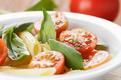 Simple italian pasta penne with tomatoes and basil Stock Image