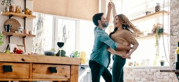 Simple joy of loving. Full length of beautiful young couple in casual clothing dancing and smiling while standing in the kitchen at home royalty free stock image
