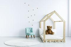 Simple kid room interior with diy bed with a teddy bear, armchair, round rug and stars on the wall. Place for your product stock photography