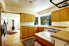 Simple kitchen interior with wooden cabinets and granite tops Royalty Free Stock Image