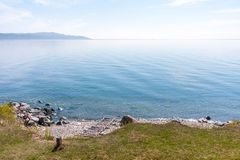 A simple landscape with an approach to water on a clear day stock image