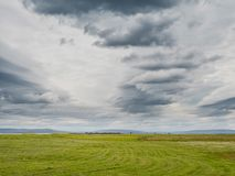 Simple landscape, Green field and dramatic cloudy sky. Freshly cut grass royalty free stock image