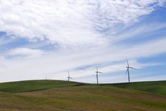 Simple landscape with wind turbines, rolling hills and cloudy blue sky. A row of wind turbines against a cloudy blue sky in a barren landscape of brown and green Royalty Free Stock Photography