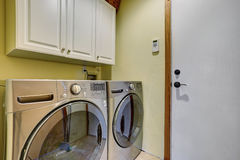 Simple laundry room with washer dryer set. Royalty Free Stock Images