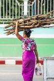 Simple life style at Tarchileik market, Eastern Myanmar. Women burmese in traditional clothing carrying a bundle of firewood on royalty free stock image