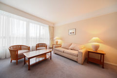 Simple light comfortable room in hotel. Soft sofa and big window Stock Photos