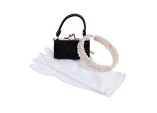 Simple luxuries. Luxuries of a pearl necklace, white gloves and black purse - path included Royalty Free Stock Photography