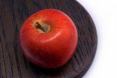 Simple matte red apple, wood. Quite large photo of a simple round apple, ripe and juicy, with tender and thin matte skin. The apple is served on some dark oak Royalty Free Stock Photography