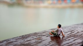 Simple, Mini figure toy old man sit at scratch wooden balcony at river side with copy or negative space for text placement area. Mini figure toy old man sit at stock image