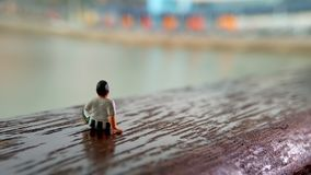 Simple, Mini figure toy old man sit at scratch wooden balcony at river side with copy or negative space for text placement area. Mini figure toy old man sit at royalty free stock photo